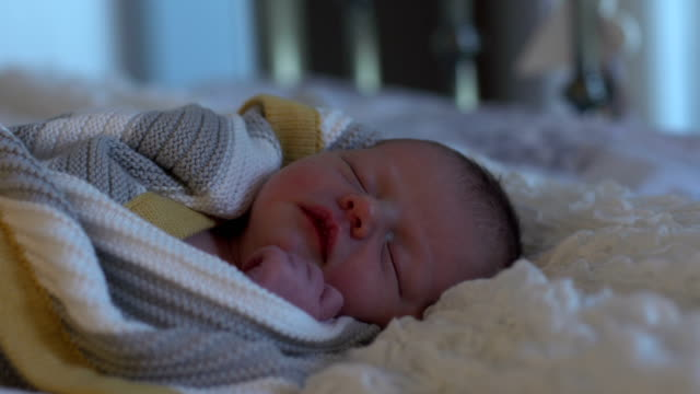 4k dolly: newborn baby wrapped in blanket asleep on bed - warm clothing stock videos and b-roll footage