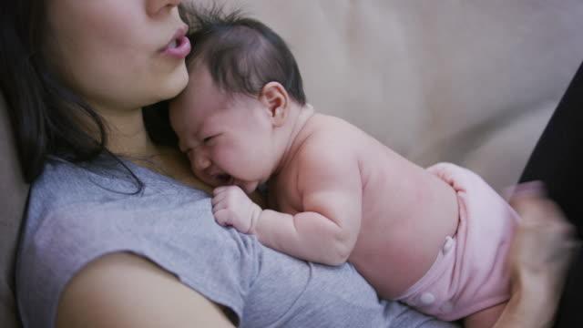 彼女の母親とあくびの新生の赤ん坊の彼女を保持します。 - 生後1ヶ月点の映像素材/bロール
