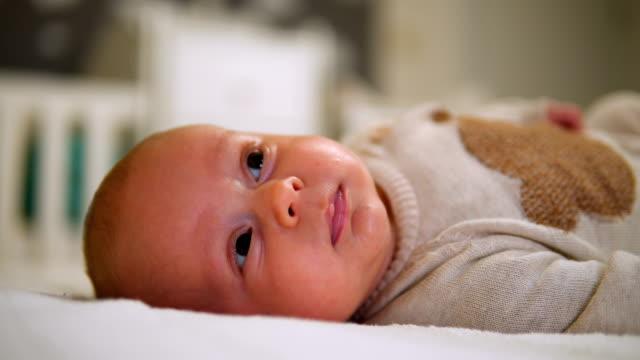 neugeborenes kind im bett entspannen. - ein männliches baby allein stock-videos und b-roll-filmmaterial