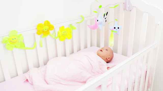 Newborn girl playing with toys in crib
