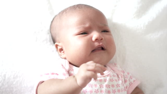 newborn is crying lying down on the white cloth. - sulking stock videos & royalty-free footage