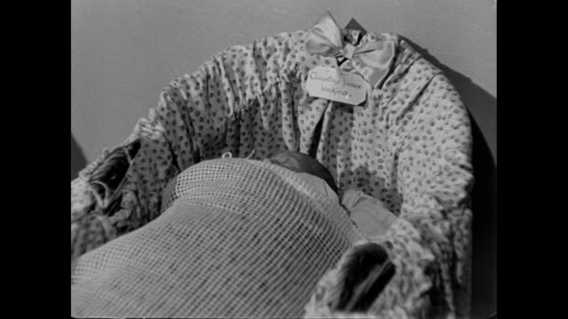 montage a newborn resting in a crib and his mother resting in a hospital bed in england during world war ii / oxford, england, united kingdom - 1946 stock videos & royalty-free footage