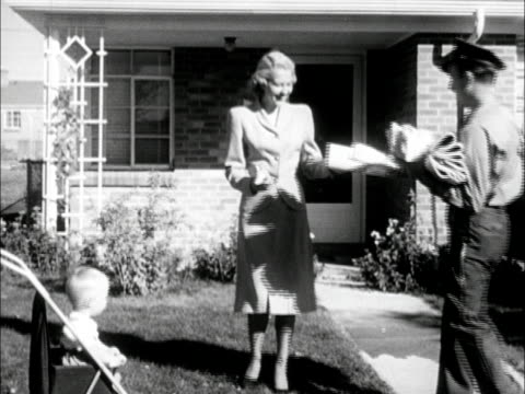 newer homes in suburban neighborhood woman in suit dress walking to greet mailman mailman handing mail to woman baby in stroller male joining woman... - suburban stock videos & royalty-free footage