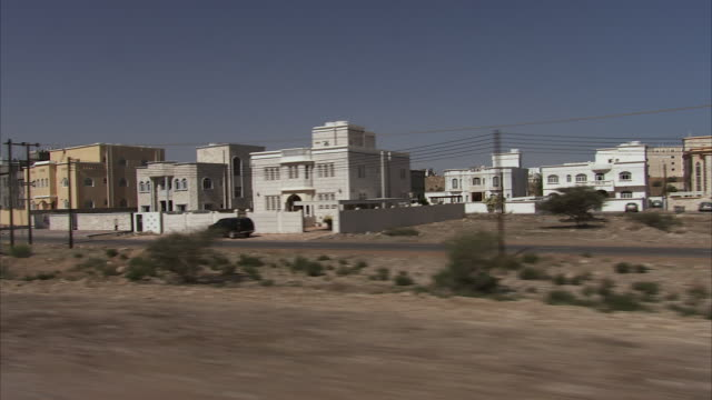 POV Newly built villas behind gated walls line in roadside / Muscat, Oman
