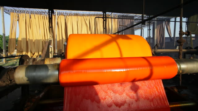Newly dyed and washed fabric spins on a roller in a Sari garment factory in Jaipur, India.