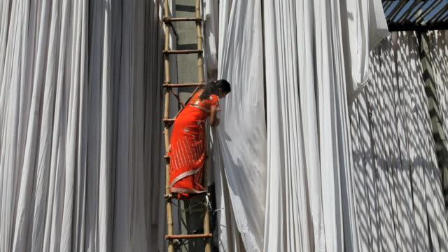 newly dyed fabric being hung up to dry, sari garment factory, rajasthan, india - sari stock videos & royalty-free footage