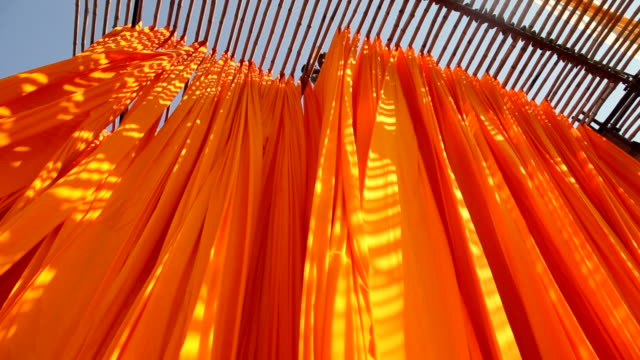 vidéos et rushes de newly dyed fabric hangs from bamboo poles to dry at the sari garment factory in jaipur, india. - dry clothes
