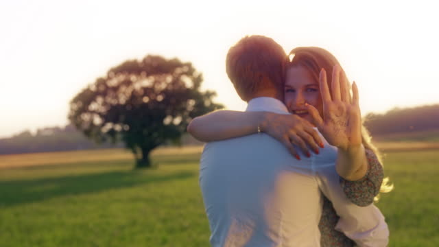 newly engaged couple embracing in meadow - yes single word stock videos & royalty-free footage