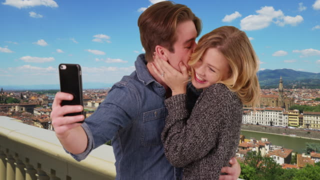 newly engaged couple taking a selfie in florence smiling and laughing - temi per la fotografia video stock e b–roll