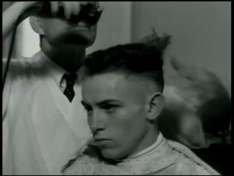 newly enlisted recruit having hair cut w/ electric shaver barber ms young man receiving buzz cut vs young men getting buzz cuts combing ext ms... - military recruit stock videos & royalty-free footage