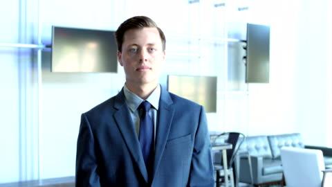 vidéos et rushes de nouvellement embauché le jeune homme en costume d'affaires regardant la caméra - tenue soignée