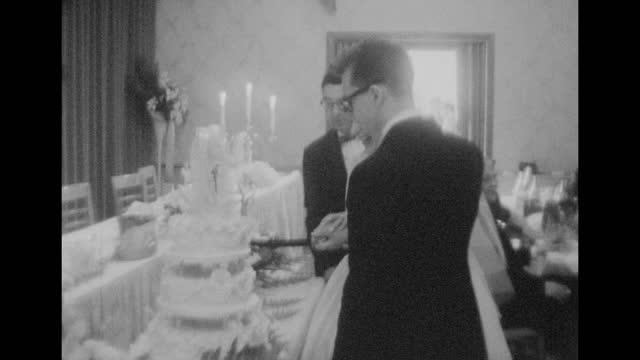 vidéos et rushes de a newly married couple cut their wedding cake together. - image en noir et blanc
