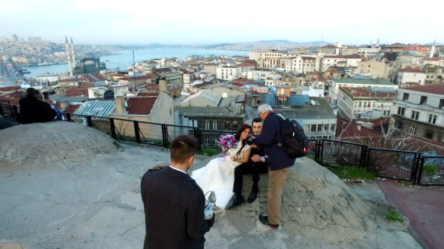 a newly married couple pose for photographs on an istanbul rooftop overlooking the city's skyline - 見渡す点の映像素材/bロール