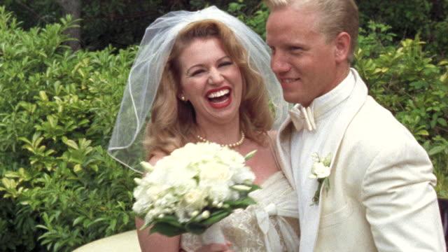 vídeos y material grabado en eventos de stock de ms newlywed bride and groom kissing near classic convertible / washington state, usa - fundido en negro
