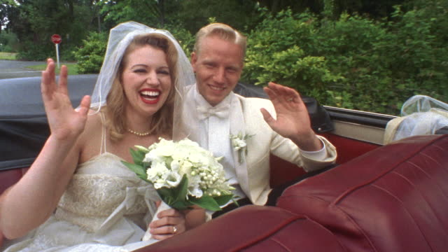 MS Newlywed bride and groom waving and kissing in backseat of moving classic convertible / Washington State, USA