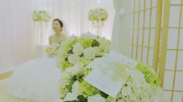 Newlywed bride sitting in the bridal dress room and talking to someone