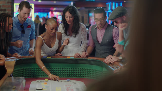 vídeos de stock e filmes b-roll de newlywed bride throws dice while playing craps with their friends and celebrates winning in a las vegas casino after eloping - jogo de lazer