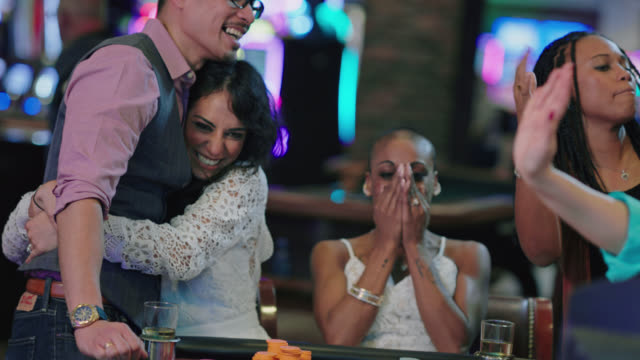 vídeos de stock e filmes b-roll de newlywed brides and their friends celebrate winning roulette in a las vegas casino after eloping - jogos de azar