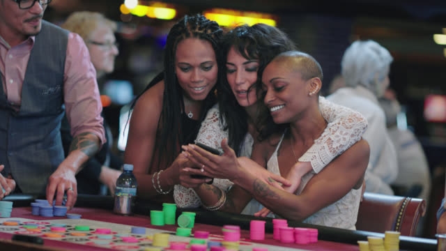 newlywed brides laugh at a selfie they took on their phone with their friends while playing roulette at a las vegas casino after eloping - gambling chip stock videos & royalty-free footage