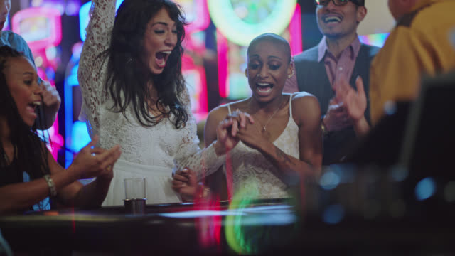 newlywed brides play blackjack with their friends in a las vegas casino after eloping and celebrate after winning - blackjack video stock e b–roll