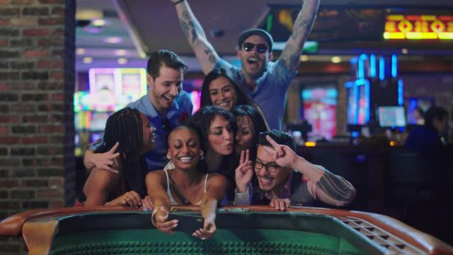 vídeos de stock e filmes b-roll de slo mo. newlywed brides take a selfie with their friends after winning craps in a las vegas casino after eloping - jogo de lazer