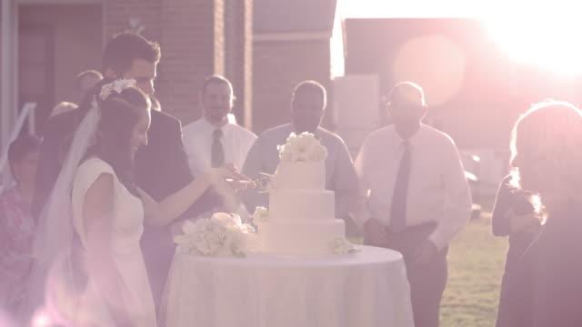 Newlywed couple cutting their wedding cake.