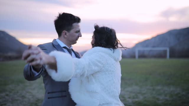 newlywed couple dancing on the field in sunset - dress stock videos & royalty-free footage