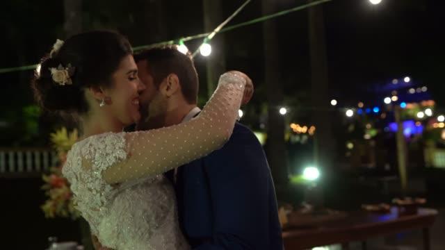 vidéos et rushes de couples nouvellement mariés dansant sous les lumières - jeunes mariés