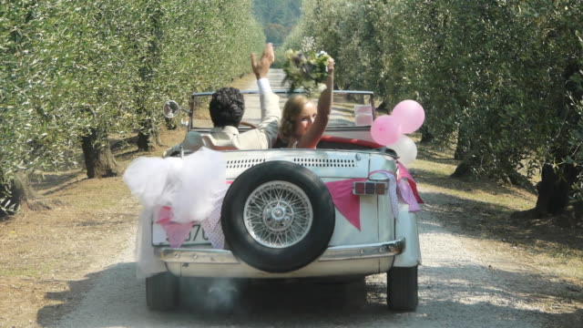 newlywed couple driving away in vintage automobile - bride 個影片檔及 b 捲影像