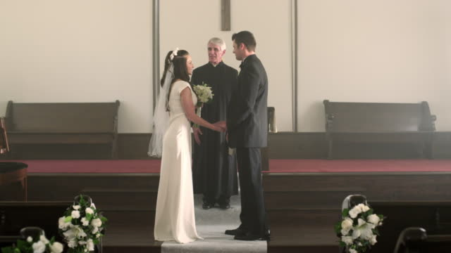 Newlywed couple kisses, turns, and walks down the aisle.