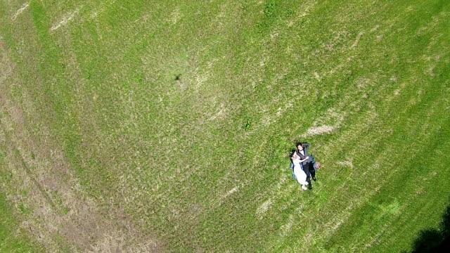 Newlywed couple lying down on grass field at Isidolmokjang Farm in Jeju Island