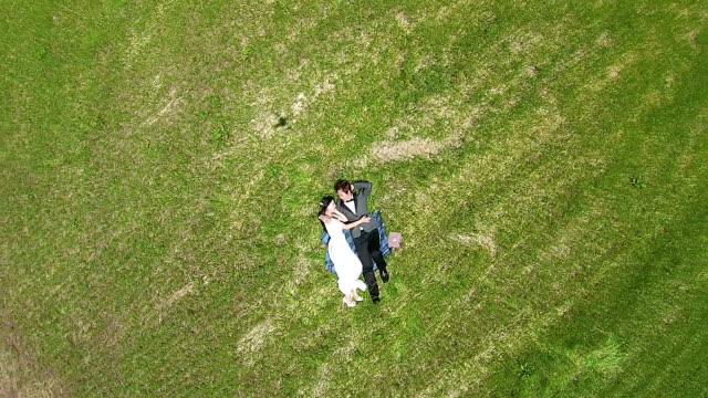 vídeos y material grabado en eventos de stock de newlywed couple lying down on grass field at isidolmokjang farm in jeju island - acostado