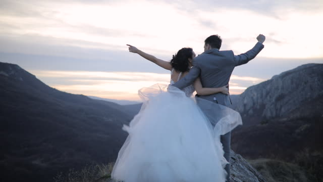 vídeos de stock e filmes b-roll de newlywed couple on mountain peak - casamento