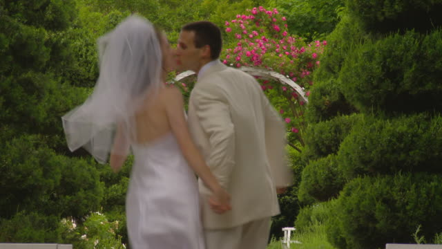 ms newlywed couple running on garden path away from camera / richmond, virginia - garden path stock videos and b-roll footage