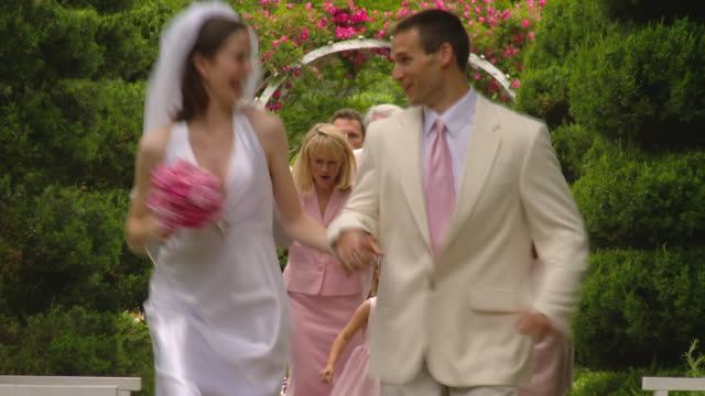 MS newlywed couple running on garden path toward camera with family following and cheering / Richmond, Virginia