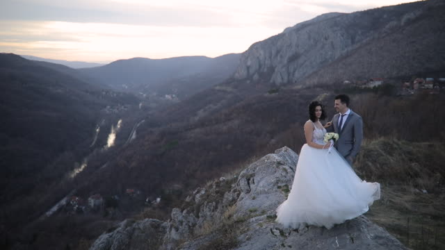 newlywed couple standing on mountain peak - uncultivated stock videos & royalty-free footage