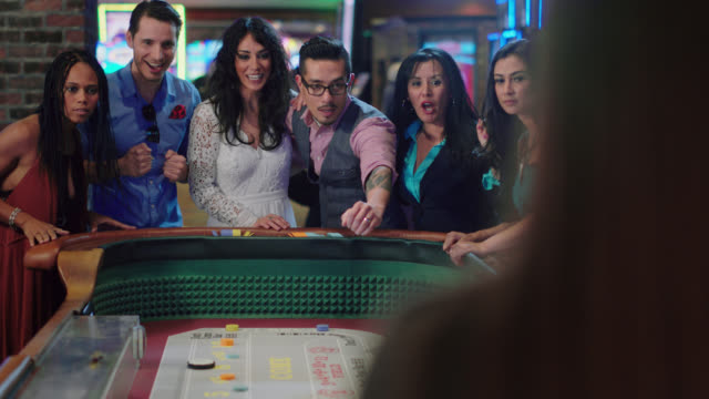 slo mo. newlywed couple throws dice while playing craps with their friends and celebrates winning in a las vegas casino after eloping - gambling chip stock videos & royalty-free footage