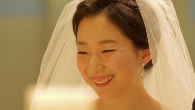 newlywed korean bride and groom smiling while they saying wedding vow - 歯を見せて笑う点の映像素材/bロール