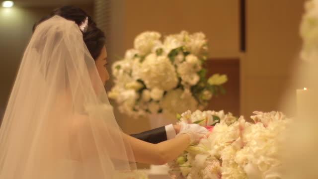 vídeos y material grabado en eventos de stock de newlywed korean couple put on their hands on the holy bible and listen to the officiant - menos de diez segundos