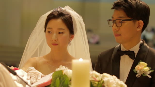 Newlywed Korean couple put on their hands on the Holy Bible while wedding vow