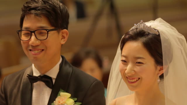 Newlywed Korean couple smiling and bowing