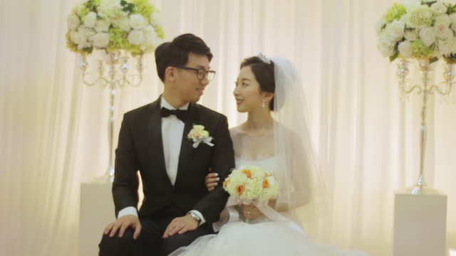 Newlywed Korean couple smiling and facing each other sitting with their arms linked
