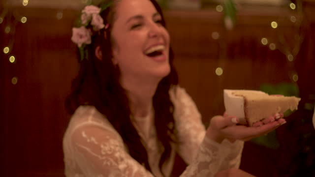 newlywed lesbian bride offering piece of wedding cake to other bride - moving down stock videos & royalty-free footage
