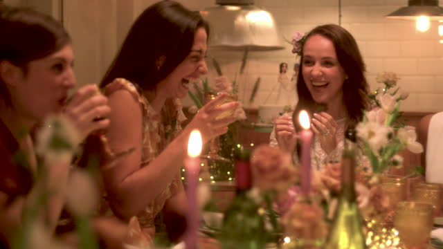 newlywed lesbian couple celebrating marriage with friends at reception dinner - five people stock videos & royalty-free footage