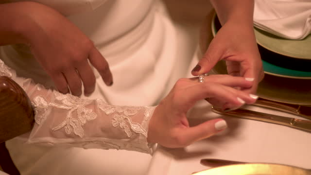 newlywed lesbian couple holding hands at wedding reception - wedding stock videos & royalty-free footage
