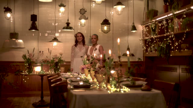 newlywed lesbian couple standing by wedding reception dinner table - three quarter length stock videos & royalty-free footage