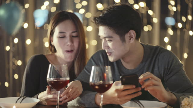 newlywed using smartphone in restaurant - candlelight stock videos & royalty-free footage