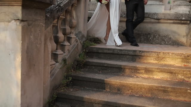 newlywed young couple holding hands and walking down the stairs - steps and staircases stock videos & royalty-free footage