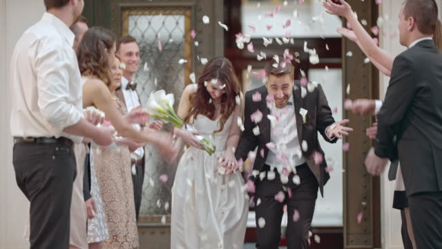 vídeos de stock e filmes b-roll de slo mo newlyweds being showered with petals when leaving church - casamento