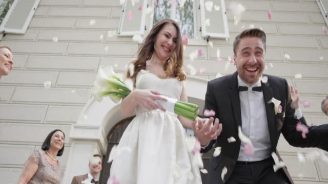 slo mo newlyweds being showered with roses when leaving church - bouquet video stock e b–roll